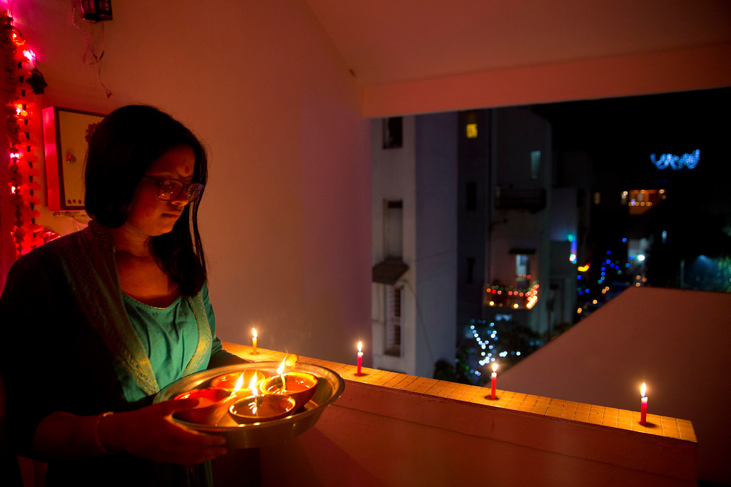 . An Indian girl holds lamps to decorate her home during Diwali festival in New Delhi, India, Thursday, Oct. 19, 2017. Diwali, the festival of lights, is being celebrated across the country Thursday. (AP Photo/Manish Swarup)