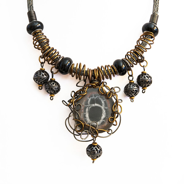 "A tightly woven handmade Viking Knit chain in a beautiful gray Hematite color supports an ancient Sepatarian Nodule. Usually you would find this ""stone"" highly polished but this particular piece has a sophisticated matte surface. A bird's nest style wire wrap holds the stone in place. Antique copper cage beads, polished black Pandora style beads and filigree dangles complete this amazing piece. Lobster style closure. This choker style necklace measures approximately 15 inches in length with an extender chain that takes it to 16 1/2 inches. A truly amazing piece of jewelry."