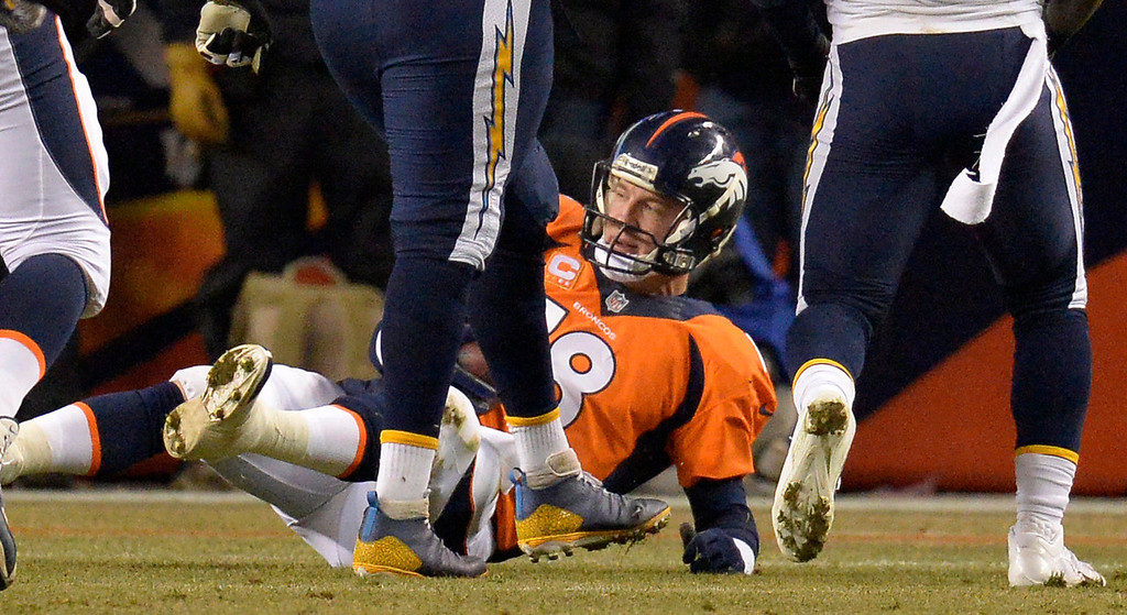 . Denver Broncos quarterback Peyton Manning (18) after being sacked  by San Diego Chargers strong safety (38) during the second quarter. The Denver Broncos vs. the San Diego Chargers at Sports Authority Field at Mile High in Denver on December 12, 2013. (Photo by John Leyba/The Denver Post)