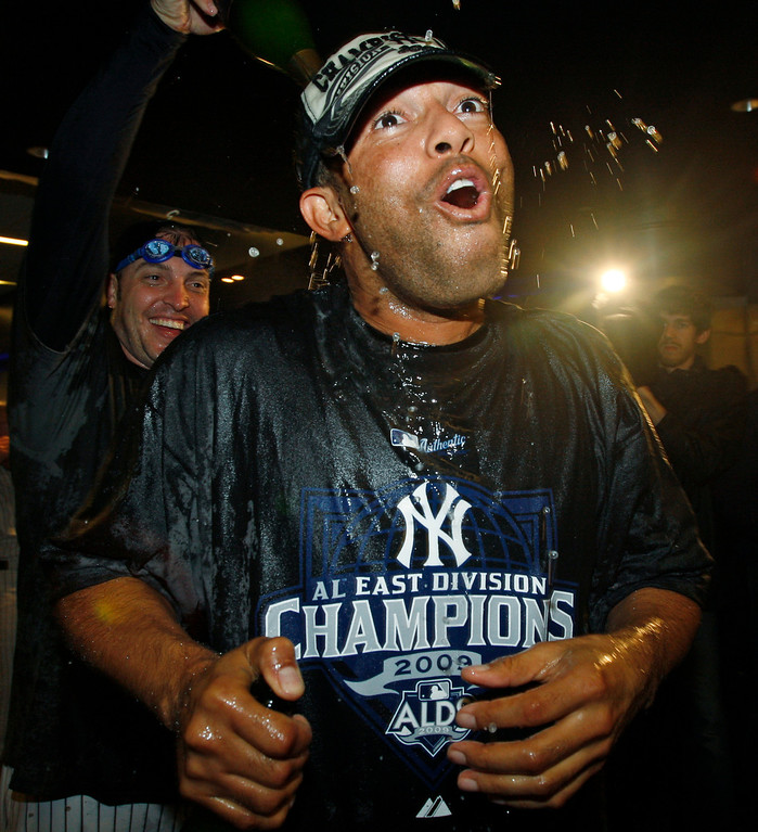 . In this Sept. 27, 2009 file photo, New York Yankees closer Mariano Rivera, foreground, reacts as outfielder Eric Hinkse pours champagne over his head as the team celebrated winning the American League East Division by beating the Boston Red Sox 4-2 in a baseball game at Yankee Stadium in New York. (AP Photo/Kathy Willens, File)