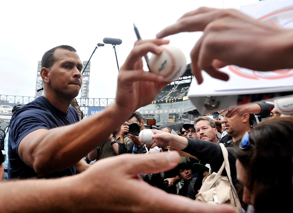 . New York Yankees\' Alex Rodriguez, left, signs autographs at U.S. Cellular Field before a baseball game against the Chicago White Sox in Chicago, Monday, Aug. 5, 2013. He was suspended through 2014 when Major League Baseball disciplined 13 players in a drug case, the most sweeping punishment since the Black Sox scandal nearly a century ago. (AP Photo/Paul Beaty)