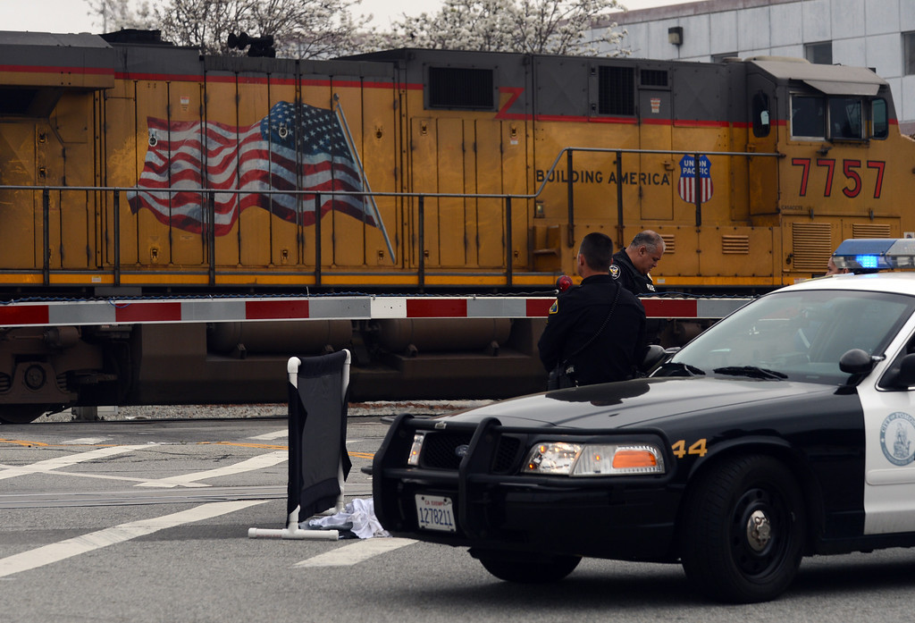 . Pomona Police investigate the scene where a pedestrian was hit and killed by a train Wednesday, March 27, 2013, at Park Ave and First Street in Pomona. Jennifer Cappuccio Maher/Staff Photographer