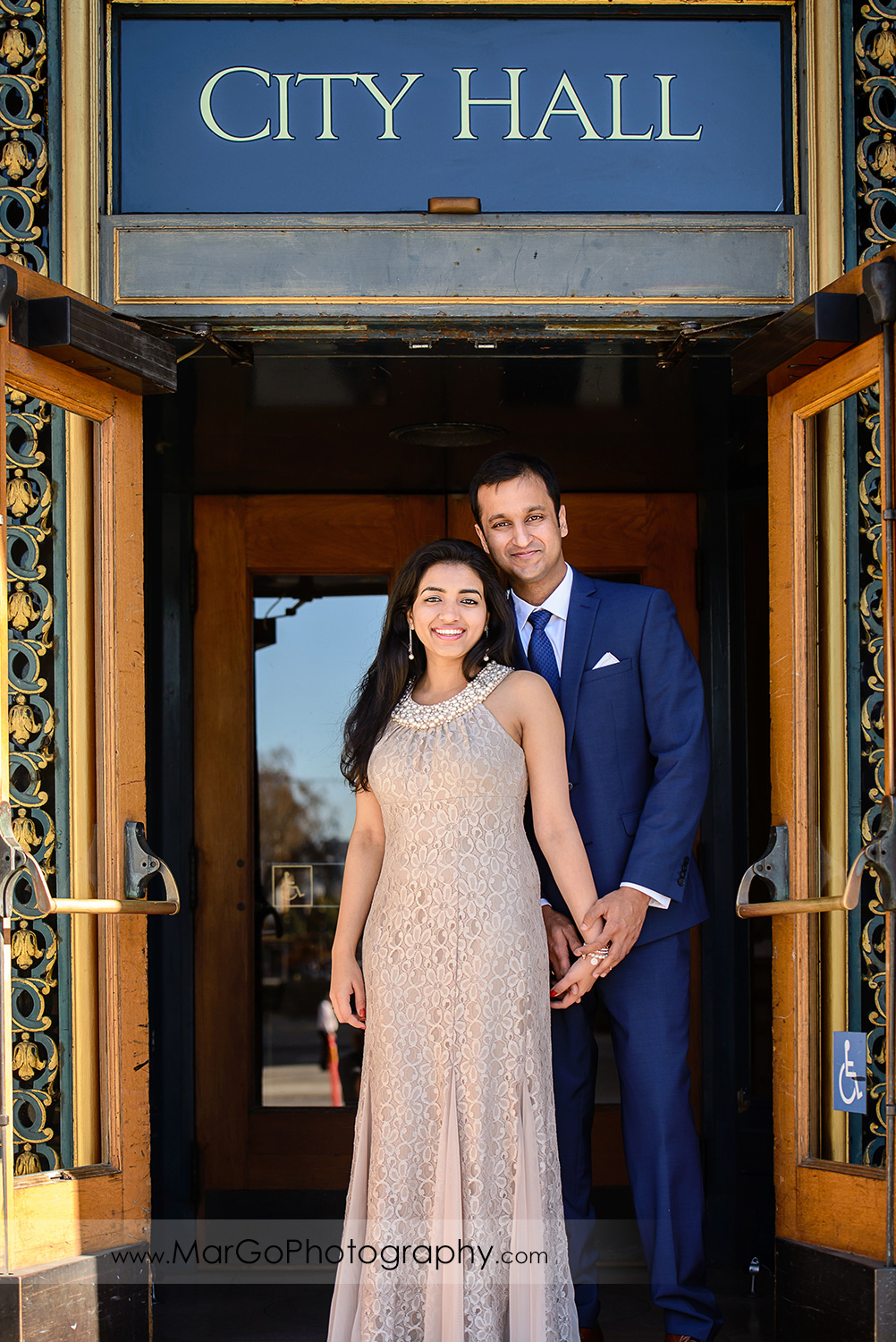portrait of woman in beige dress and man in navy blue suit in San Francisco City Hall entrance door