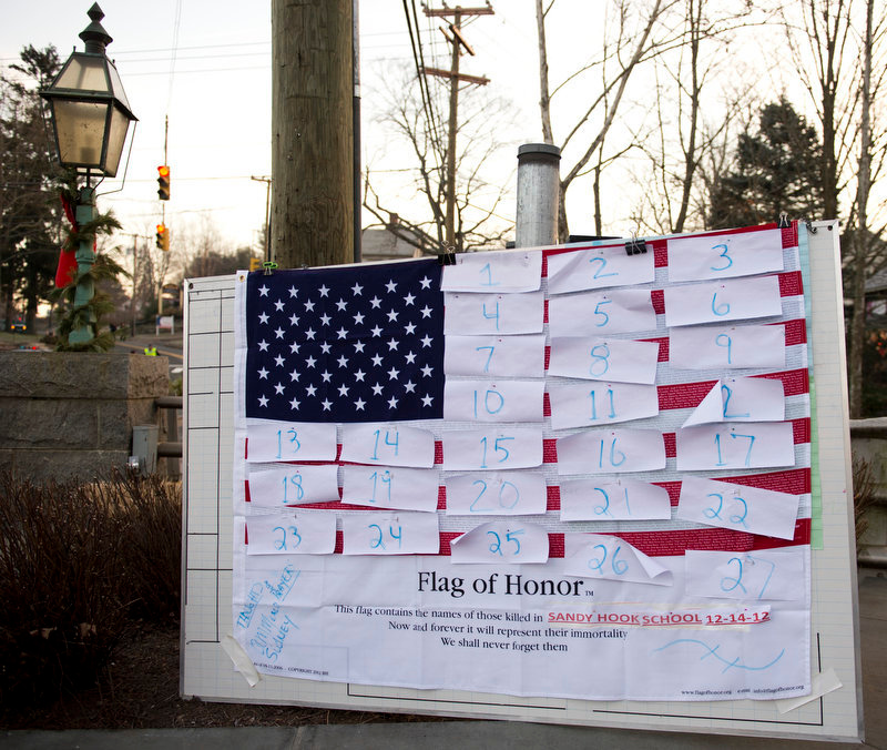 . A flag hanging in the business area of town waits for victims\' names on December 15, 2012 in Newtown, Connecticut. The residents of an idyllic Connecticut town were reeling in horror from the massacre of 20 small children and six adults in one of the worst school shootings in US history. The heavily armed gunman shot dead 18 children inside Sandy Hook Elementary School, said Connecticut State Police spokesman Lieutenant Paul Vance. Two more died of their wounds in hospital.      DON EMMERT/AFP/Getty Images