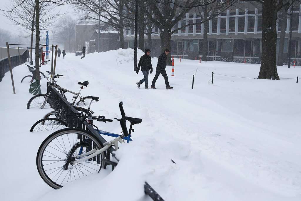 . Pedestrians walk through campus at Harvard University on January 27, 2015 in Cambridge, Massachusetts. Boston, and much of the Northeast, is being hit with heavy snow from Winter Storm Juno.  (Photo by Maddie Meyer/Getty Images)