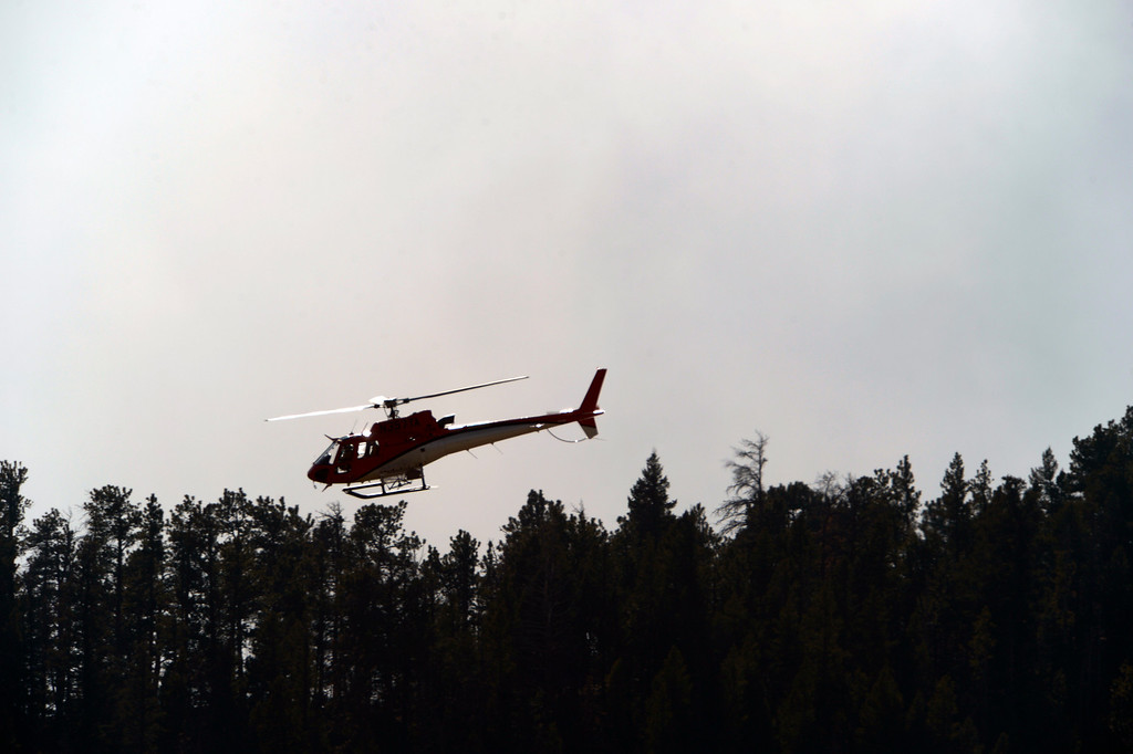 . A reconnaissance helicopter flies near the fire.  Officials are worried about winds kicking up later in the afternoon on December 2, 2012.