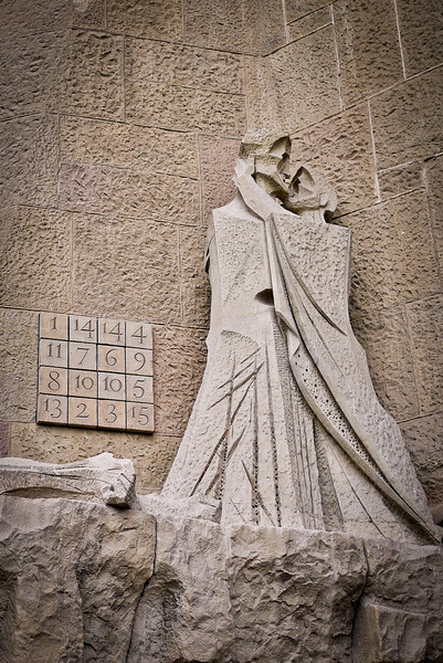 Guant figures embrace on the  Passion façade of La Sagrada Familia in Barcelona, Spain