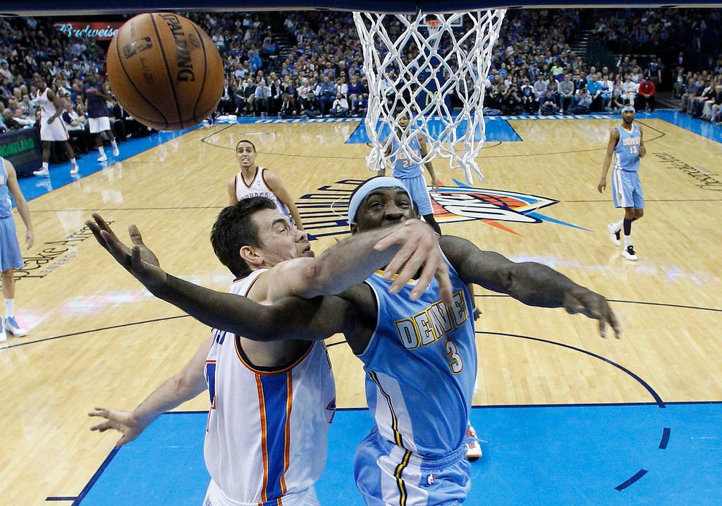 . Denver Nuggets guard Ty Lawson (3) is fouled by Oklahoma City Thunder forward Nick Collison (4) as he shoots in the second quarter of an NBA basketball game in Oklahoma City, Tuesday, March 19, 2013. Denver won 114-104. (AP Photo/Sue Ogrocki)