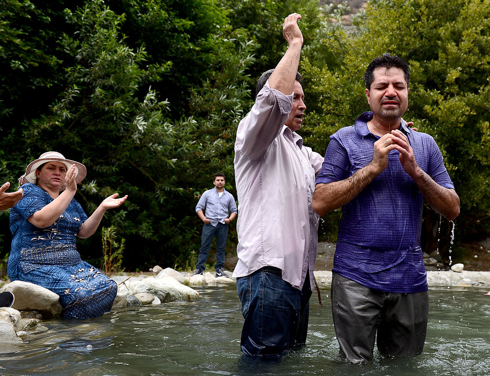 . Pastor Jesus Rodriguez, of Iglesia del Dios Vivo in La Puente, baptizes Enrique Estrada, of La Puente, in the San Gabriel River along the East Fork of the Angeles National Forest Saturday, July 20, 2013. The Urban Conservation Corps educates people visiting the East Fork of the San Gabriel River in the Angeles National Forest. Although the Urban Conservation Corps says their river trash count studies show less trash the area is still littered with garbage. (SGVN/Staff Photo by Sarah Reingewirtz)