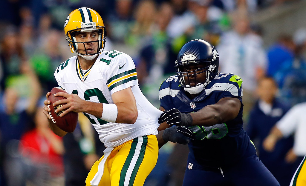 . SEATTLE - SEPTEMBER 04: Quarterback Aaron Rodgers #12 of the Green Bay Packers is sacked by defensive end Cliff Avril #56 of the Seattle Seahawks during the third quarter of the game at Century Link Field on September 4, 2014 in Seattle, Washington.  (Photo by Jonathan Ferrey/Getty Images)