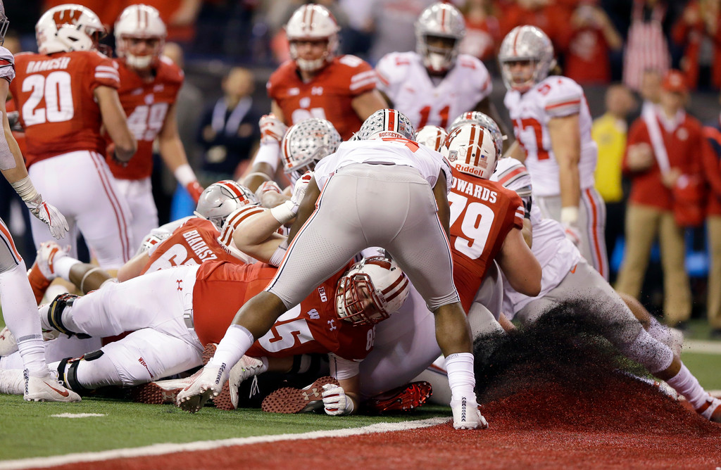 . A section of turf comes up as Wisconsin running back Chris James scores during the second half of the Big Ten championship NCAA college football game against Ohio State, Saturday, Dec. 2, 2017, in Indianapolis. (AP Photo/Michael Conroy)