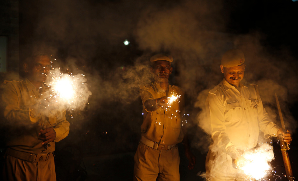 . Indian policemen play with firecrackers to celebrate Diwali, the Hindu festival of lights, in Allahabad, India, Thursday, Oct. 19, 2017. Hindus light lamps, wear new clothes, exchange sweets and gifts and pray to goddess Lakshmi during Diwali, the festival of lights. (AP Photo/Rajesh Kumar Singh)