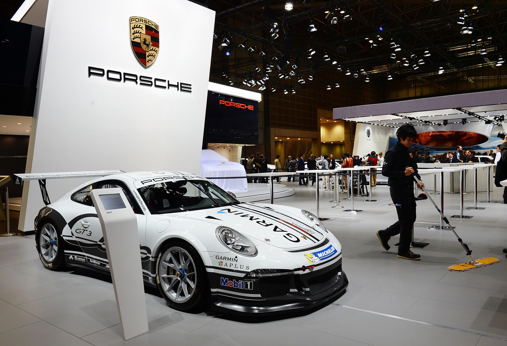 """. A Porsche worker cleans the floor beside a \""""911 GT3\"""" race car at the company\'s booth at the Tokyo Motor Show in Tokyo on November 20, 2013.      AFP PHOTO / TOSHIFUMI KITAMURA/AFP/Getty Images"""