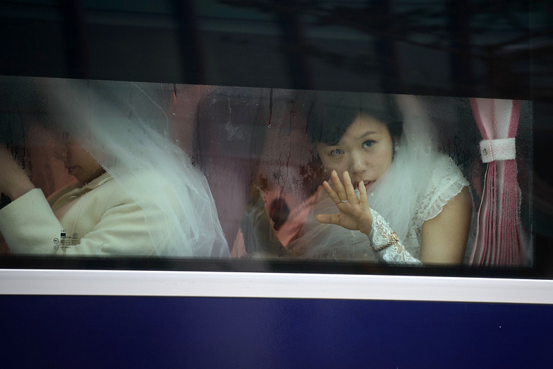 ". A bride looks from the window of a bus as she arrives for a mass wedding event held by the Unification Church in Gapyeong on February 12, 2014. Unification Church members forming 2500 couples from 52 countries were married in a mass wedding in South Korea -- only the second such event since the death of their ""messiah\"" and controversial church founder Sun Myung Moon. (ED JONES/AFP/Getty Images)"