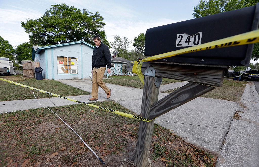 . An engineer stands in front of a home where sinkhole opened up on Friday, March 1, 2013, in Seffner, Fla. (AP Photo/Chris O\'Meara)