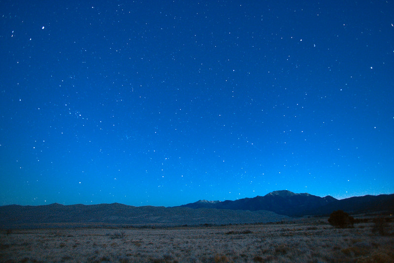A starry night spreads out across the sky  above the dune field of  the Great Sand Dunes National Park and Preserve.