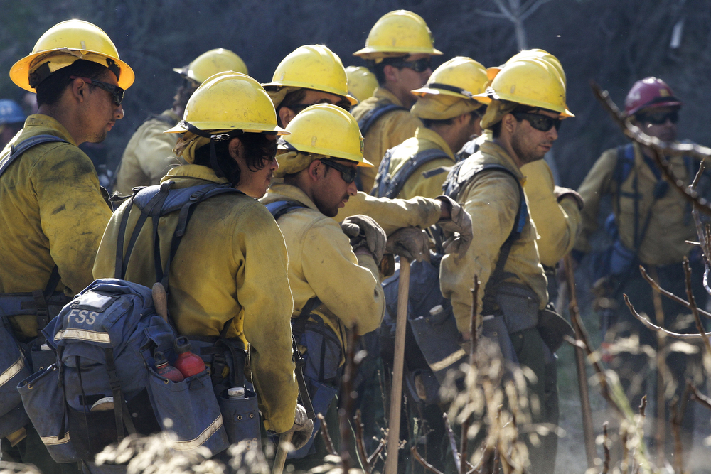 . Members of a U.S. Forest Service hand crew take a break from clearing fire break lines at the Colby Fire  on a hillside above Highway 39 on January 17, 2014 in Azusa, California. Three men have been arrested and charged with starting the fire that has now destroyed 1,700 acres of land and several homes around Glendora and Azusa in the San Gabriel Valley near Angeles National Forest, prompting officials to order evacuations for houses near the fire. (Photo by Jonathan Alcorn/Getty Images)