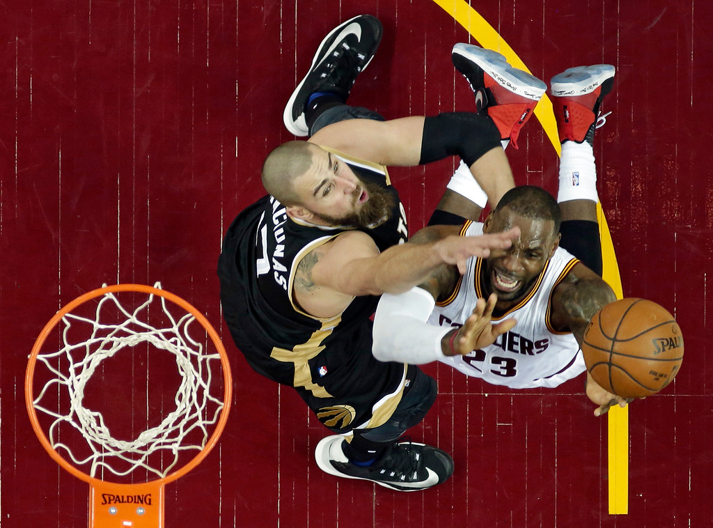 . Toronto Raptors\' Jonas Valanciunas, left, from Lithuania, defends Cleveland Cavaliers\' LeBron James during the first half in Game 2 of a second-round NBA basketball playoff series, Wednesday, May 3, 2017, in Cleveland. (AP Photo/Tony Dejak)