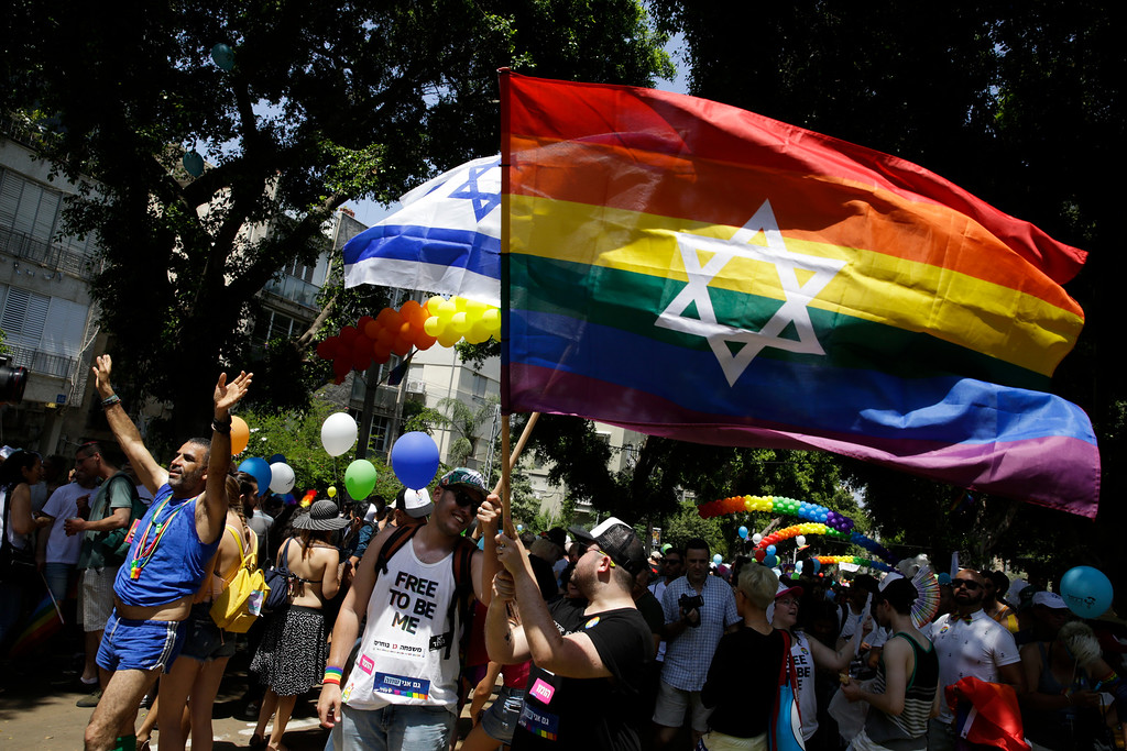 . Israelis and tourists wave flags as they participate in the Gay Pride parade in Tel Aviv, Israel, Friday, June 8, 2018. (AP Photo/Sebastian Scheiner)