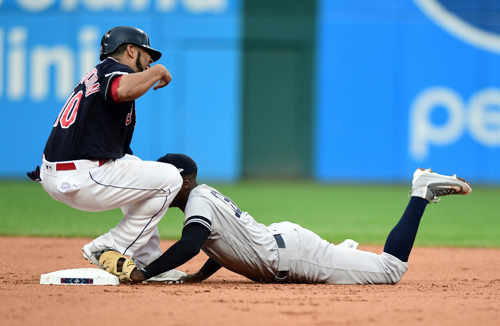 . Cleveland Indians\' Edwin Encarnacion rolls his ankle trying to get back to second base as New York Yankees\' Didi Gregorius tries to make the tag in the second inning of Game 2 of baseball\'s American League Division Series, Friday, Oct. 6, 2017, in Cleveland. (AP Photo/David Dermer)