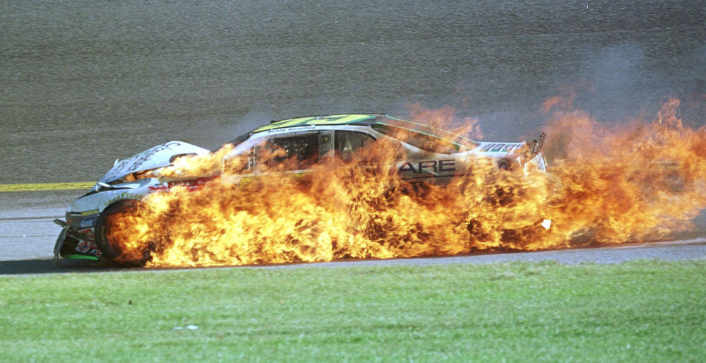 Description of . Bobby Hamilton's No.55 is engulfed in flames as he passes turn 2 on the 149th lap after a 17-car crash during the 2002 Daytona 500 at Daytona International Speedway in Daytona Beach, Fla., Sunday, Feb. 17, 2002. (AP Photo/Russell Williams)
