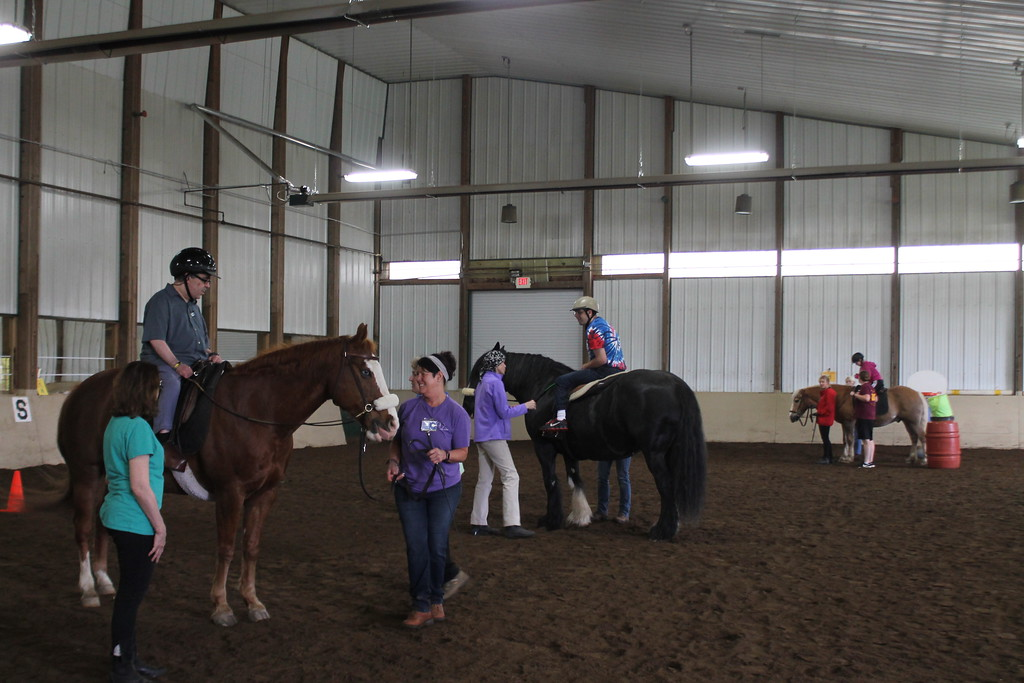 . Clients from the Willoughby  Branch ride in an equine therapy program designed to teach coordination and other skills while guided  by volunteers at Fieldstone Farm. Kristi Garabrandt - The News-Herald