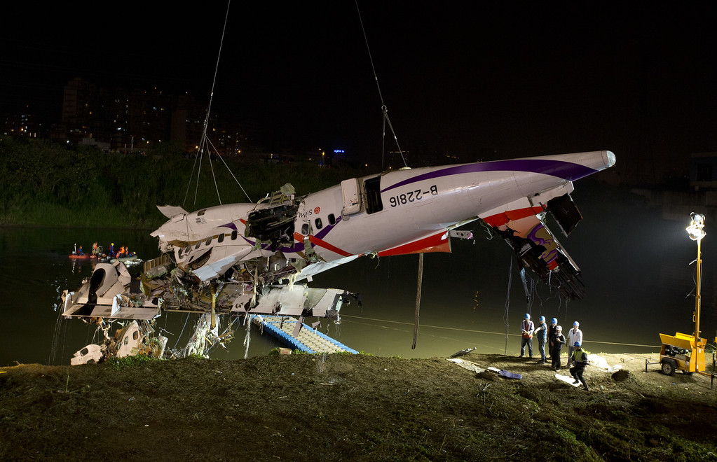 . Rescuers lift the wreckage of the TransAsia ATR 72-600 out of the Keelung river at New Taipei City on February 4, 2015. At least 23 people were killed when a passenger plane operated by TransAsia Airways clipped an overpass soon after take-off and plunged into a river in Taiwan, the airline\'s second crash in seven months.  (Photo by Ashley Pon/Getty Images)