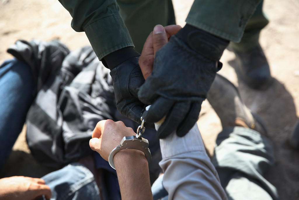 . MISSION, TX - APRIL 11:  A U.S. Border Patrol agent handcuffs an undocumented immigrant near the U.S.-Mexico border on April 11, 2013 near Mission, Texas. A group of 16 immigrants from Mexico and El Salvador said they crossed the Rio Grande River from Mexico into Texas during the morning hours before they were caught. The Rio Grande Valley sector of has seen more than a 50 percent increase in illegal immigrant crossings from last year, according to the Border Patrol. Agents say they have also seen an additional surge in immigrant traffic since immigration reform negotiations began this year in Washington D.C. Proposed refoms could provide a path to citizenship for many of the estimated 11 million undocumented workers living in the United States. Photo by John Moore/Getty Images)  (Photo by John Moore/Getty Images)