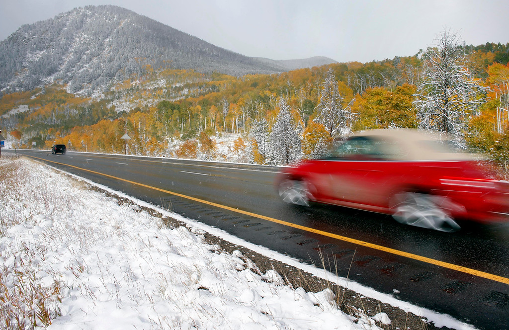 . A car passes golden Aspen leaves and fresh snow covering the roadside along I-70 near Frisco, Colo., Friday Oct. 4, 2013. Powerful storms moved into the Midwest on Friday due to a cold weather system gaining strength as it traveled east from Colorado and Wyoming. (AP Photo/Brennan Linsley)