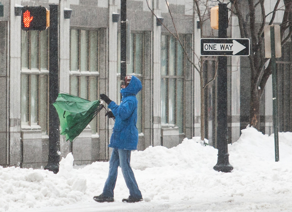 . A man fights with his umbrella as he walks down Delaware avenue , in downtown Wilmington, Del. on Thursday morning, Feb. 13, 2014. The city saw nearly a foot of snow fall over night, and residents were forced to dig out in blowing sleet in the morning. (AP Photo/The News Journal, Kyle Grantham)