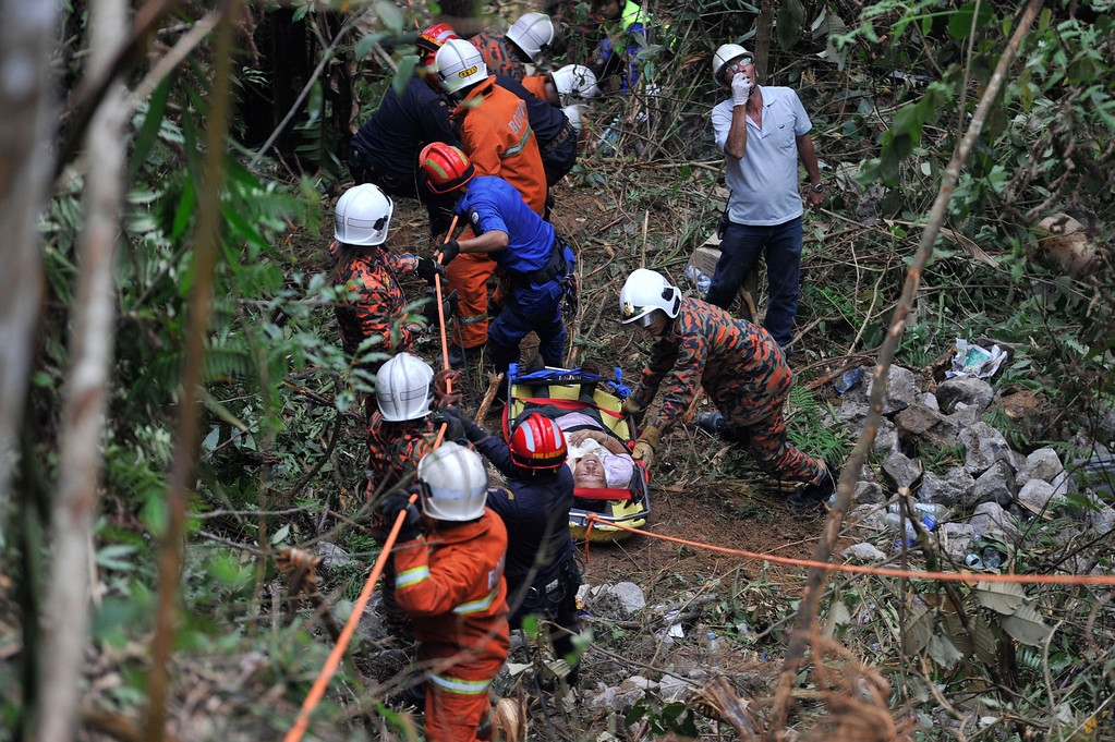 . Malaysian emergency services personnel rescue a passenger (C) after a bus carrying tourists and local residents fell into a ravine near the Genting Highlands, about an hour\'s drive from Kuala Lumpur on August 21, 2013.   AFP PHOTOSTR/AFP/Getty Images