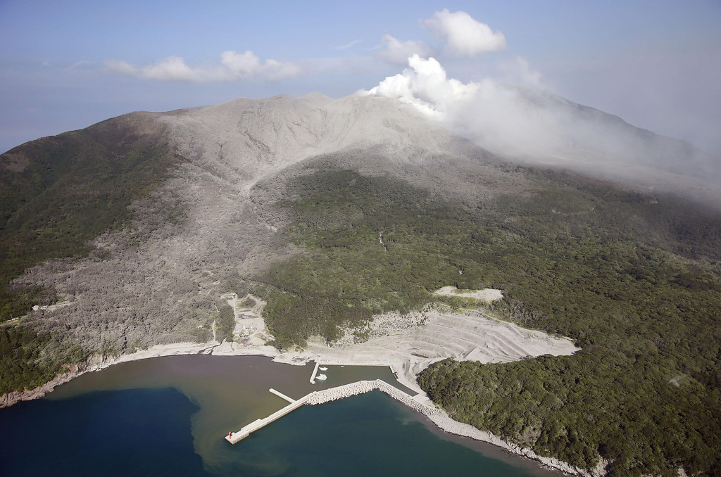 . A column of white smoke rises from Mount Shindake on Kuchinoerabu island, southern Japan, Friday, May 29, 2015. The volcano erupted in spectacular fashion on the small island on Friday, spewing out rocks and sending black clouds of ash 9 kilometers (5.6 miles) into the sky. Authorities told people on the island to evacuate. The mountain slope covered by gray color is believed to be marked by pyroclastic flows of rock and hot gases. (Kyodo News via AP)