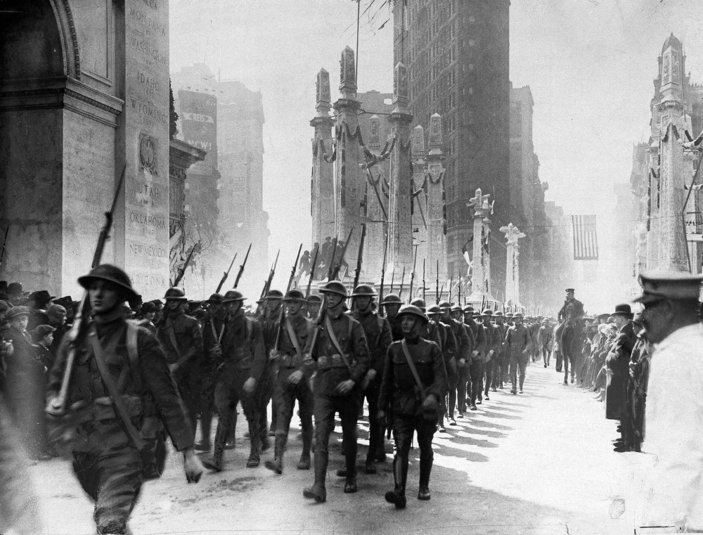 Description of . Soldiers returned to the U.S. from France after the Great War march in a homecoming parade in Madison Square, New York City, 1918. In the background is the Flatiron building. (AP Photo)