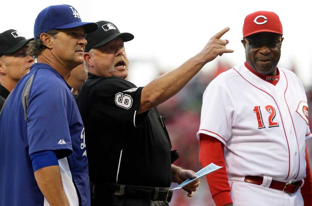 . Home plate umpire Jim Joyce goes over the ground rules with Los Angeles Dodgers manager Don Mattingly, left, and Cincinnati Reds manager Dusty Baker prior to a baseball game, Friday, Sept. 6, 2013, in Cincinnati. (AP Photo/Al Behrman)