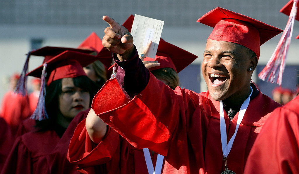 . A graduate points towards the stands during the Whittier High School graduation at Whittier College in Whittier, Calif., on Wednesday, June 4, 2014.  (Keith Birmingham/Pasadena Star-News)
