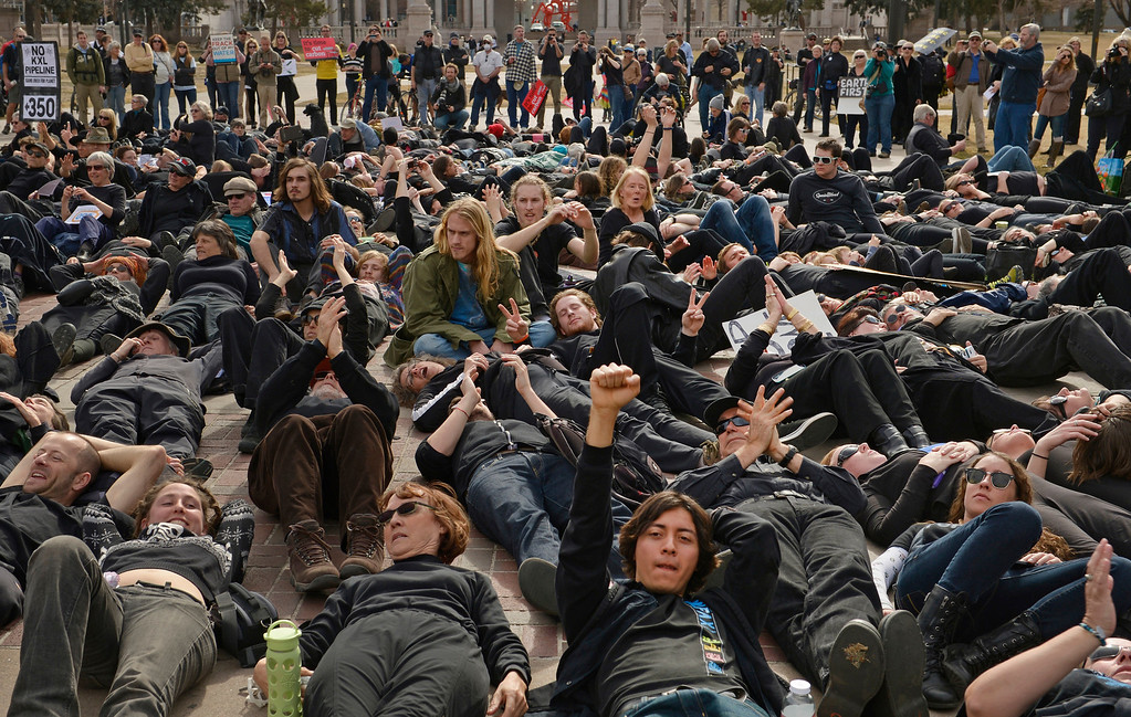 . DENVER, CO- FEBRUARY 17:   Issac Rivera, with hand in the air, and the other protestors wore black and lay down in Civic Center park to act as a human oil spill during the rally.  A few hundred people from a coalition of students, faith-based organizations, indigenous, political, and environmental groups marched from the Denver Auraria campus and ended in a rally at Civic Center Park on February 17th, 2013.  The march, called the #ForwardOnClimate Solidarity March and rally, organized by the Sierra Club, 350.org and GoFossilFree.org,  coincided with tens of thousands of protestors, who converged on Washington, DC for the largest climate rally in history. Denver was one of 18 cities hosting major actions to show solidarity with the DC event.    (Photo By Helen H. Richardson/ The Denver Post)