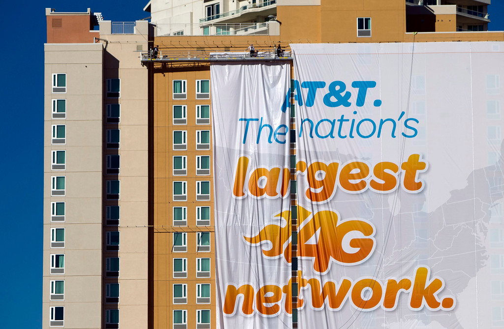 . Workers put up a banner advertisement for AT&T on the side of a hotel as they prepare for International CES show in Las Vegas, Nev., on Jan. 4, 2013. (REUTERS/Steve Marcus)