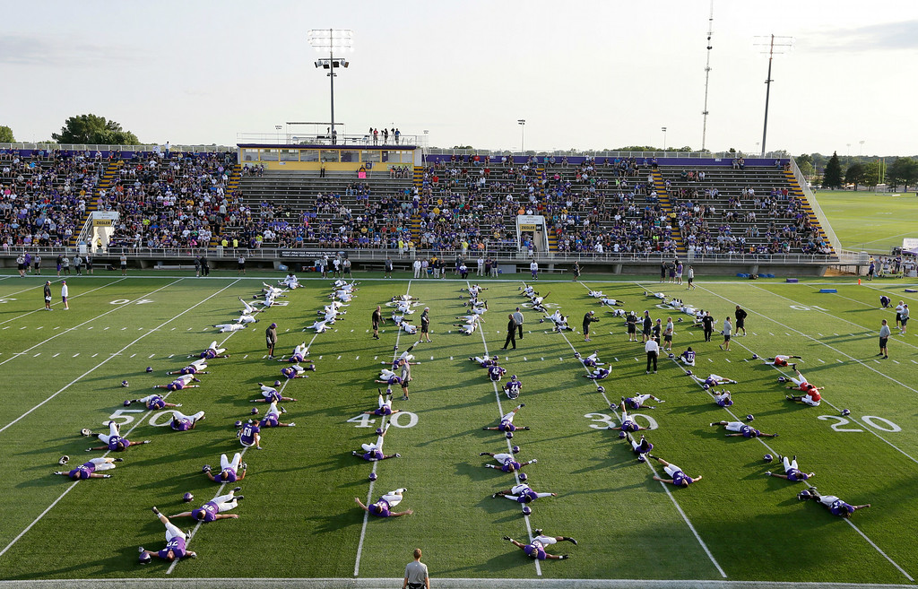 . Minnesota Vikings players stretch on the field during an NFL football training camp practice, Monday, July 28, 2014, in Mankato, Minn. (AP Photo/Charlie Neibergall)