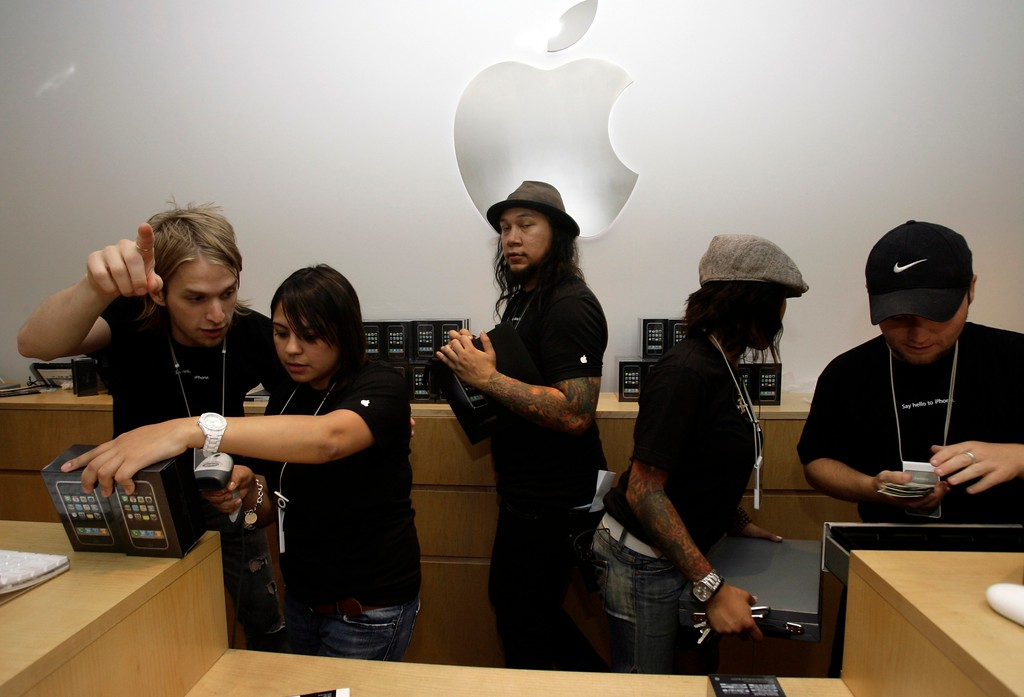 . Apple cashiers rush to ring iPhones as they are sold Friday, June 29, 2007 inside the Apple store at The Grove in Los Angeles. The iPhone\'s price tag: $499 for a 4-gigabyte model and $599 for an 8-gigabyte version, on top of a minimum $59.99-a-month two-year service plan with AT&T. (AP Photo/Damian Dovarganes)