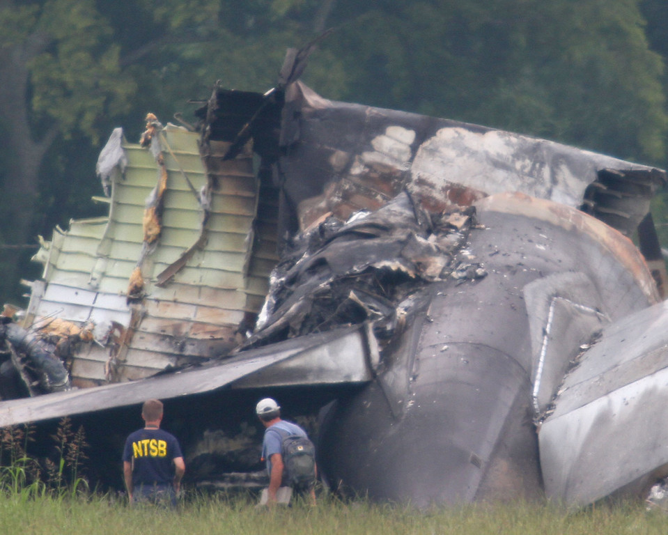 . An NTSB investigator and an unidentified person look over the tail section of the UPS cargo plane that crashed Wednesday on approach to the Birmingham-Shuttlesworth International Airport, Thursday, Aug. 15,  2013 in Birmingham, Ala.  (AP Photo/Hal Yeager)