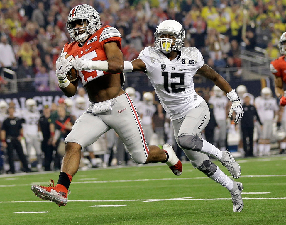 . Ohio State\'s Ezekiel Elliott runs past Oregon\'s Chris Seisay for a touchdown during the first half of the NCAA college football playoff championship game Monday, Jan. 12, 2015, in Arlington, Texas. (AP Photo/Eric Gay)