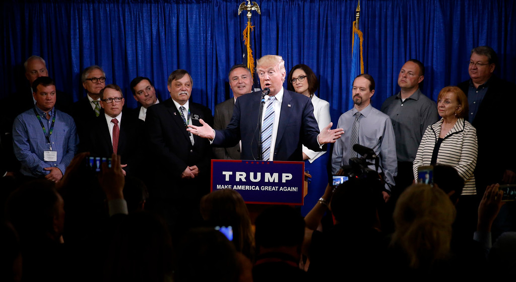 . Republican presidential candidate Donald Trump, center, stands with some of the 22 delegates from North Dakota to the Republican National Convention, who are the core of delegates that elevated Trump over the 1237 needed for the GOP\'s presidential nomination, Thursday, May 26, 2016, in Bismarck, N.D. (AP Photo/Charles Rex Arbogast)