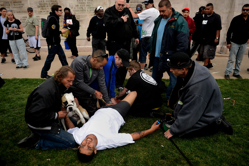 . DENVER, CO. - APRIL 20: April 20: Denver Paramedics, Denver Police officers and good samaritans at the scene attend to a shooting victim at Civic Center Park in Denver Colorado, Saturday April 20th, 2013 after the 4/20 pot rally. Two people were shot during Saturday\'s annual 4/20 marijuana rally, held on a day cannabis enthusiasts regard as a holiday called 4/20 that drew tens of thousands to Denver\'s Civic Center park. This is the first 4/20 marijuana rally since Colorado voters legalized marijuana use for people 21 and older in November. April 20, 2013 Denver, Colorado. (Photo By Joe Amon/The Denver Post)