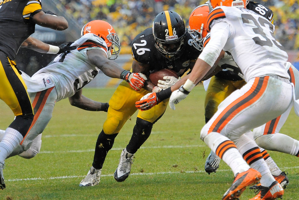 . Pittsburgh Steelers running back Le\'Veon Bell (26) runs between Cleveland Browns defensive back Julian Posey (38), left, and cornerback Jordan Poyer (33) for a touchdown in the second quarter of an NFL football game on Sunday, Dec. 29, 2013, in Pittsburgh. (AP Photo/Don Wright)