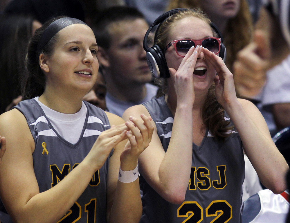 . Mount St. Joseph\'s Lauren Hill, right, cheers on her team with teammate Brooke Mosler during her first NCAA college basketball game against Hiram University at Xavier University in Cincinnati on Sunday Nov 2, 2014. The NCAA allowed Mount St. Joseph\'s season opener to be moved up to Nov. 2, so that Hill, who has an inoperable brain tumor, to be able to play in a college basketball game. Hill is wearing sunglasses to protect her eyes from the bright lights. Hill is wearing ear and eye protection to help her with the lights and noise. (AP Photo/Tom Uhlman)