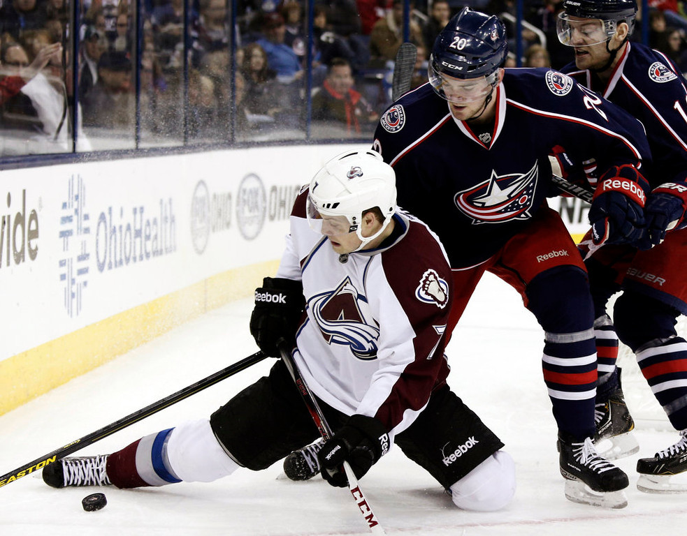 . Colorado Avalanche\'s John Mitchell, left, works for the puck against Columbus Blue Jackets\' Tim Erixon in the first period of an NHL hockey game in Columbus, Ohio, Sunday, March 3, 2013. (AP Photo/Paul Vernon)