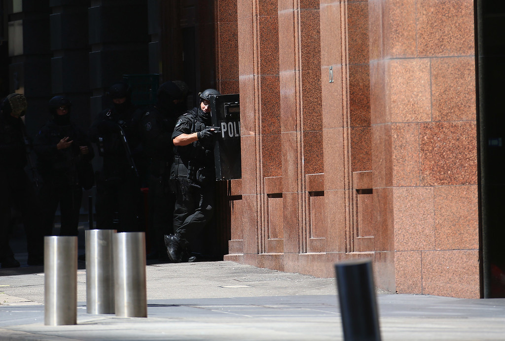 . SYDNEY, AUSTRALIA - DECEMBER 15:  Armed police patrol the vicinity at Lindt Cafe, Martin Place on December 15, 2014 in Sydney, Australia.  Major landmarks in Sydney, including the Sydeny Opera House, have been evacuated as police respond to a hostage situation inside a Martin Place cafe.  (Photo by Don Arnold/Getty Images)