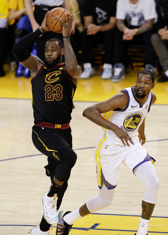 . Cleveland Cavaliers forward LeBron James (23) passes in front of Golden State Warriors forward Kevin Durant (35) during the second half of Game 1 of basketball\'s NBA Finals in Oakland, Calif., Thursday, May 31, 2018. (AP Photo/Marcio Jose Sanchez)