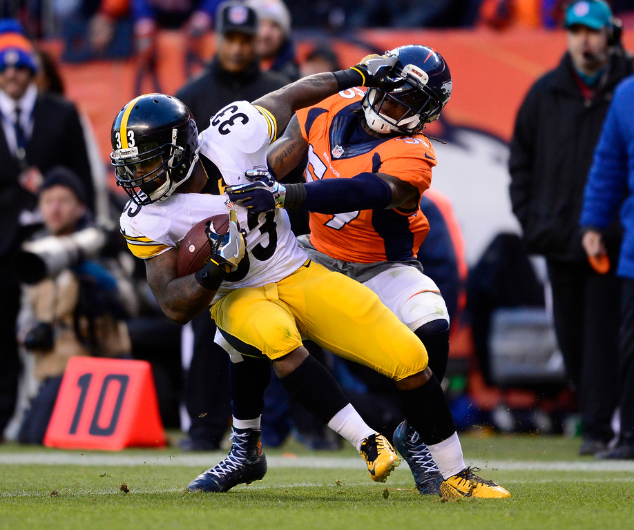 . Pittsburgh Steelers running back Fitzgerald Toussaint (33) stiff arms Denver Broncos inside linebacker Danny Trevathan (59) as he tries to get away from his tackle during the third quarter January 17, 2016 in the Divisional Round Playoff game at Sports Authority Field at Mile High Stadium. (Photo By Eric Lutzens/The Denver Post)