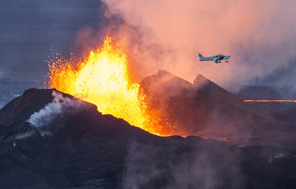 . An aerial picture taken on September 14, 2014 shows a plane flying over the Bardarbunga volcano spewing lava and smoke in southeast Iceland. The Bardarbunga volcano system has been rocked by hundreds of tremors daily since mid-August, prompting fears the volcano could explode. Bardarbunga, at 2,000 metres (6,500 feet), is Iceland\'s second-highest peak and is located under Europe\'s largest glacier, Vatnajoekull. AFP PHOTO /  BERNARD  MERIC/AFP/Getty Images